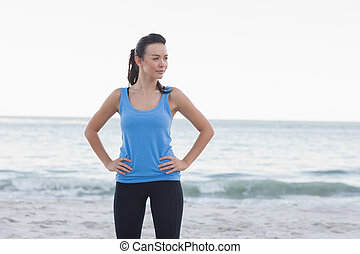 Happy brunette woman standing in front of the sea