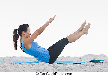 Woman doing pilates on exercise mat at beach
