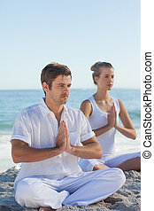 Man and woman practicing yoga on the beach on a sunny day