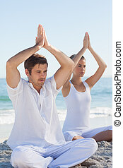 Concentrated woman and man practicing yoga at beach on a...