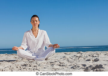 Woman in white doing yoga on the beach