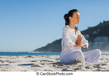 Calm woman practicing yoga on the beach on a sunny day