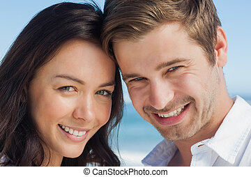 Close up view of couple smiling at camera at beach on a...