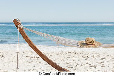 Shot of a straw hat lying on hammock against ocean