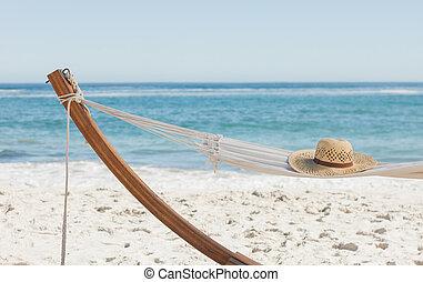 Shot of a straw hat lying on hammock against ocean