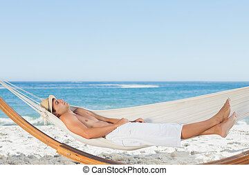 Handsome man relaxing in a hammock on the beach behind on...