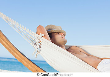 Man lying on hammock sleeping with straw hat on face on...