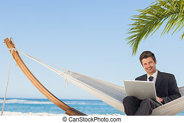 Businessman sitting in hammock using laptop looking at...