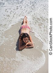 High angle view of woman lying down on beach and looking at...
