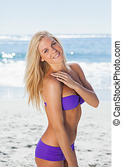 Blonde woman posing and smiling at camera on beach on...