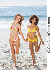 Happy women having fun on the beach in front of the ocean