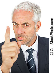 Angry businessman pointing his finger and looking at camera...
