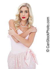 Severe blonde model in pink dress posing holding her...