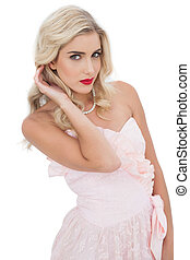 Unsmiling blonde model posing touching her hair on white...
