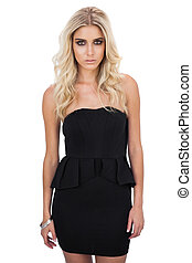 Unsmiling blonde model in black dress posing looking at...