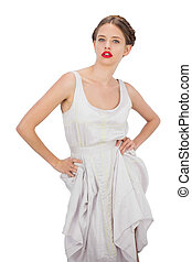 Severe model in white dress posing hands on the hips on...