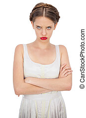 Frowning model in white dress posing with crossed arms on...