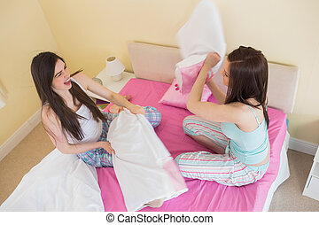 Happy friends in pajamas having a pillow fight on bed in...