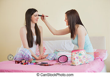 Smiling girl giving her friend a makeover at sleepover in...
