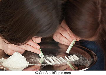 Two girls snorting an illegal white powder with dollar bills...
