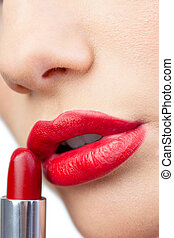 Extreme close up on gorgeous red lips being made up
