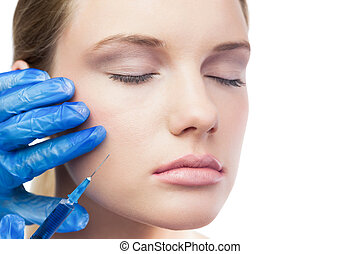 Relaxed cute model having botox injection on the cheek -...