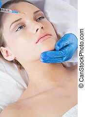 Surgeon making injection on forehead on relaxed woman lying...