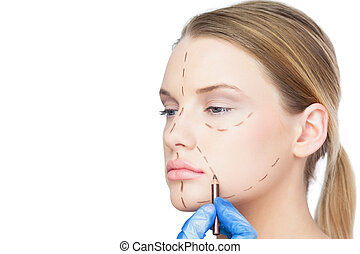 Surgeon drawing dotted lines on pretty patient before...