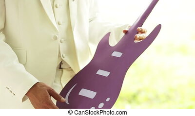 Game on toy guitars - Newly married couple play lined lilac...