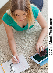 Woman lying on floor doing her homework using tablet at home...