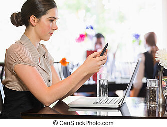 Businesswoman texting on phone in a restaurant