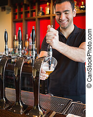 Handsome barkeeper pulling a pint of beer and smiling behind...
