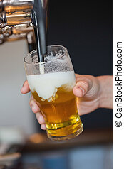 Hand holding glass filling beer pouring from a beer tap