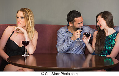 Blonde woman feeling alone as two people are flirting beside...