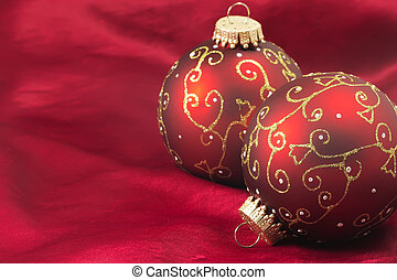 Two red christmas bulbs on a red background