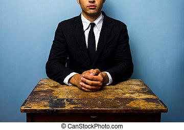 Businessman sitting at old wooden desk