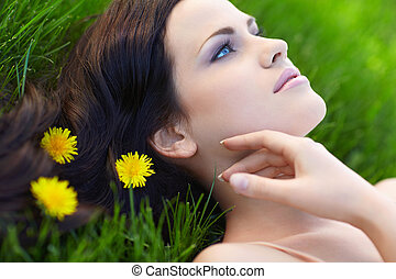 Beauty - Young girl on grass with flowers