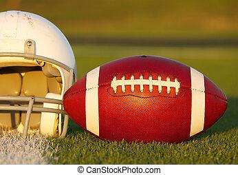 Football and Helmet on the Field