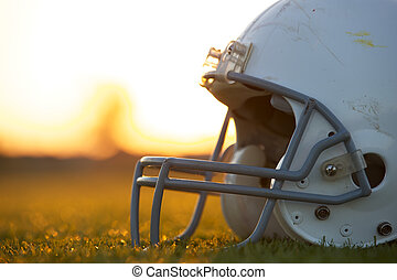 American Football Helmet on the Field at Sunset with room...