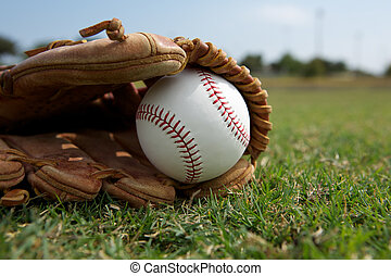 Baseball in a Glove on the Field - Baseball in a Glove with...
