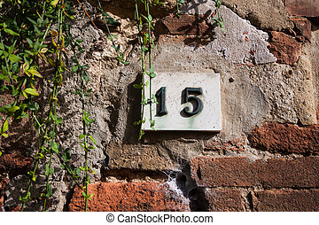 three dimensional house number fifteen. Black lettering on a...