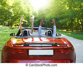 Happy free couple driving in red retro car cheering joyful...