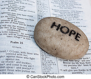 open bible with prayer rock - a beige rock with the word...