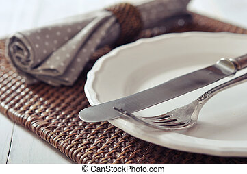 Cutlery - White plate, fork and knife on wicker wooden...