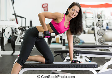 Girl in health club - young women do a workout at the gym...