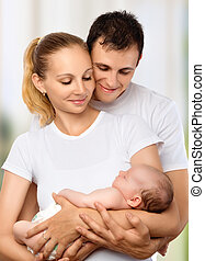 happy young family of mother, father and newborn baby in...