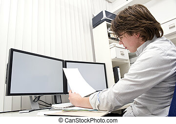 Studying a document - A designer, studying a ducument from...