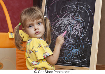 Sad girl draws by a chalk on the ea
