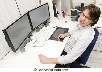 Designer at work - A designer at work behind two monitors,...