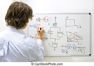 Engineer at whiteboard - An engineer drawing a complexe...